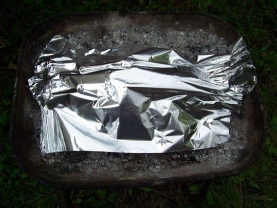 On entoure les oignons de braises et cendres, puis on les recouvre d'une feuille d'alu