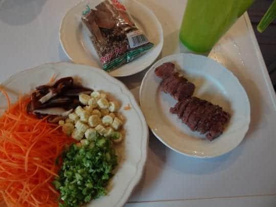 Légumes, viande émincée, sachet d'épices pour pho et les nouilles qui trempent dans un pichet